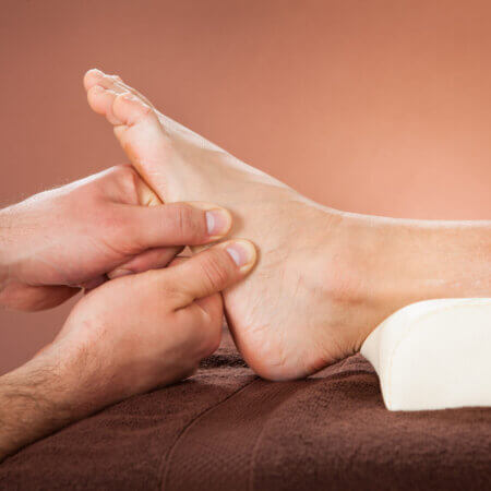 Cropped image of male therapist giving foot massage to female customer at beauty spa