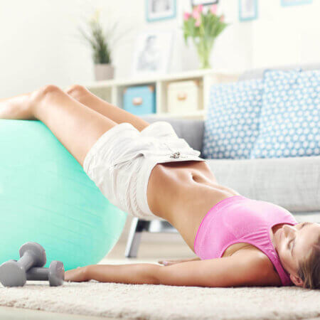 Fit girl doing sit-ups at home